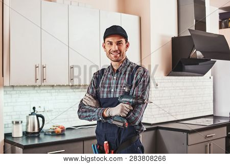 Modern Handyman. Portrait Of A Smiling Male Foreman Standing With Perforator