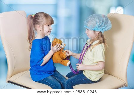 A Closeup Of Children Playing Patient And Pediatrician Who Is Touching A Toy Bear With Her Stethosco