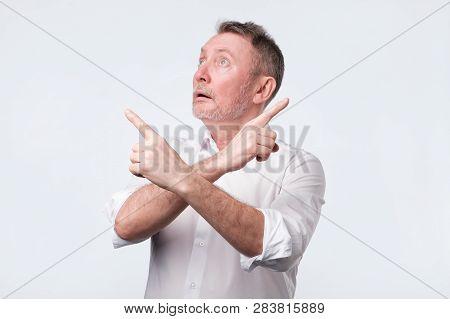 Senior Man Feeling Uncertain Having Two Choices.