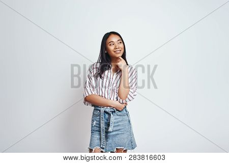 What If... Curious Asian Young Woman In Casual Wear Is Smiling, Touching Her Chin And Thinking What