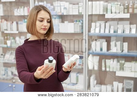 Cutomer choosing medical products for health care and wellbeing. Beautiful woman thinking, holding two white cosmetic bottles in hands. Woman standing in drugstore. poster