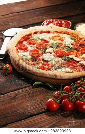 Pizza With Tomatoes, Mozzarella Cheese, Black Olives And Basil. Delicious Italian Pizza On Wooden Pi