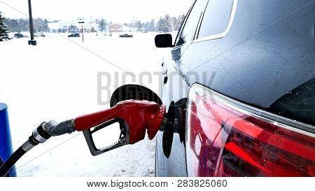 Fuel Nozzle With Red Handle, Filling Gas Tank Of Black Car During Winter Snow Storm In Minnesota.