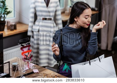 Dark-haired Smiling Asian Lady In A Dark-blue Blouse Choosing A Perfume