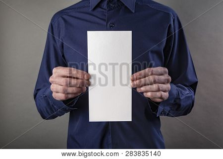 A Man In A Blue Shirt Holding A White Booklet