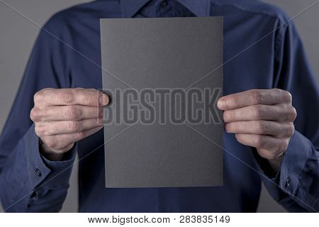 A Man In A Blue Shirt Holding A Black Booklet