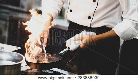 Chef Cooking With Flame In A Frying Pan On A Kitchen Stove, Chef In Restaurant Kitchen At Stove With