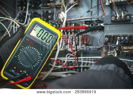 Electrician Is Checking The Voltage In The Electrical Circuit Of The Installation With A Multimeter.
