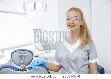 Stomatologist Young Female Standing In Dentist Office And Looking At Camera. Portrait Of Smiling Doc