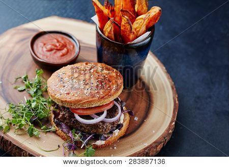 Homemade burger with whole grain bun and sweet potato fries