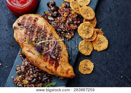 Grilled chicken breast with quinoa,black beans and banana chips and chili sauce
