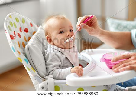 family, food, eating and people concept - father feeding little baby sitting in highchair with puree by spoon at home