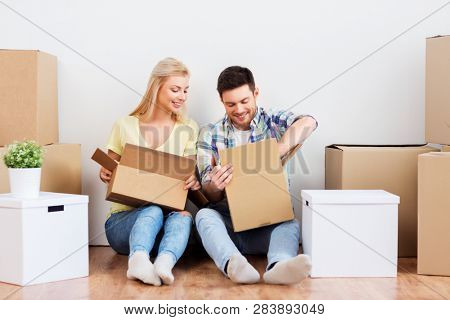 mortgage, moving and real estate concept - happy couple unpacking boxes at new home
