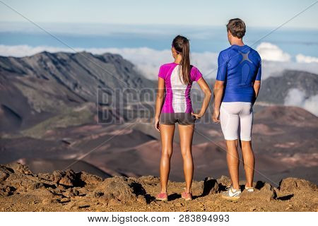 Fit athletes man and woman standing on mountain summit looking down at landscape view of volcano mountains background. Fitness hikers couple in sportswear.