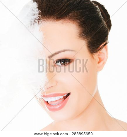 Woman face covered in half by delicate feather, on white background.
