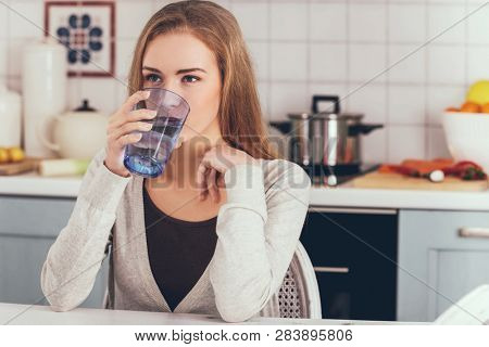 Woman sitting in kitchen and drinking mineral water from glass.