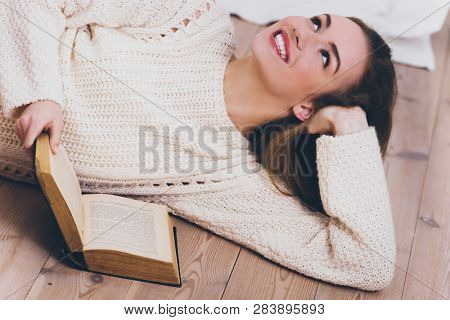 Woman lying on floor with book and looking away while dreaming.