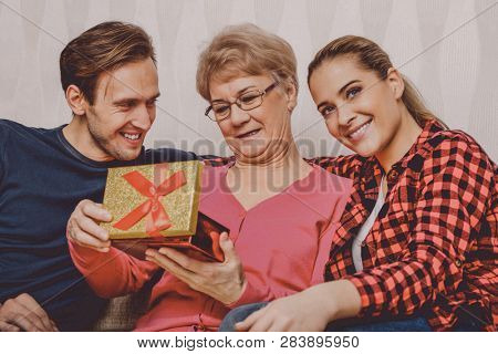 Grandchildren are giving a present to her grandmother. Family connections.