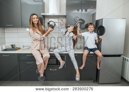 Young woman and her children are sitting on the kitchen set and playing with kitchen utensils at the home. Family home shoot. Childhood. Kid's fashion.