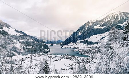 beautiful winter scenery with snowy village and frozen lake in the swiss alps