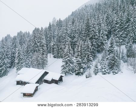 moody winter scenery of a snow covered house in a forest