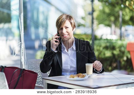 Front View Of A Elegant Smiling Business Woman Sitting On A Chair In A Coffee Shop While Using A Mob