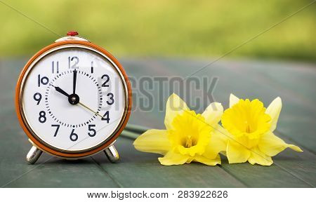 Daylight Savings Time, Spring Forward - Web Banner Of A Retro Alarm Clock And Easter Flowers