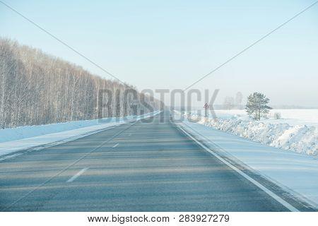 Asphalt Road In Winter In The Forest. Asphalt Under The Snow. Road In The Snow. Winter Road.