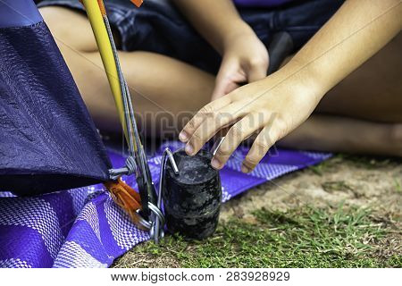 Hand Of A Child Holding A Rubber Hammer Hammered Steel Mounting Tent Down On The Ground.