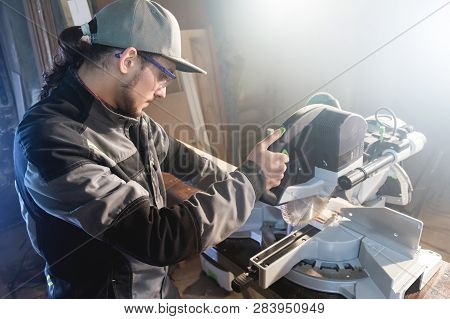 Young Brunette Man Wearing A Cap In A Gray Jacket By Profession A Carpenter Cuts Wooden Boards With