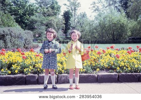 Cheshire, Uk - Circa, April, 1968: Vintage Photo Of Two Happy Young Girls Standing In Front Of A Col