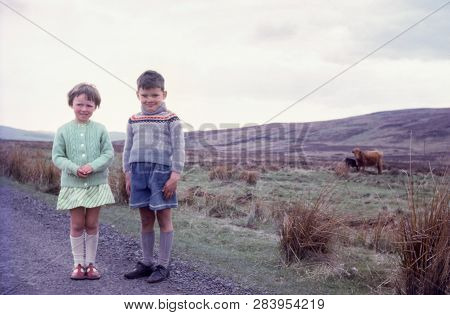 Highlands Of Scotland, Uk - Circa, 1969: Vintage Photo Of A Young Boy And Girl Standing In The Cold