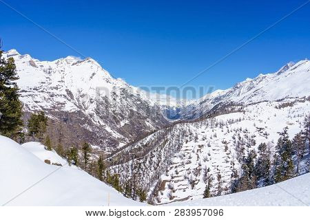 Single Backcountry Skier In A Vast Mountain Landscape On His Way Down From A High Summit With A Grea