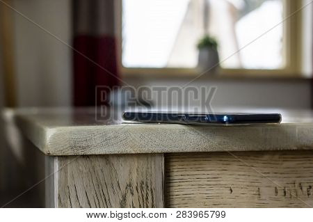 Mobile Phone Is Lying Dangerously On The Edge Of A Wooden Table Against The Background Of A Window,