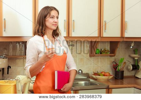 Relax And Rest In Kitchen. Middle Aged Woman Chef Housekeeper Holding Cookbook With Cup Of Tea Coffe