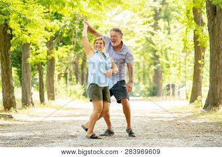 Portrait Of A Beautiful Happy Senior Couple In Love Dancing In The Park