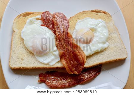 Poached Eggs On White Toast With Streaky Bacon
