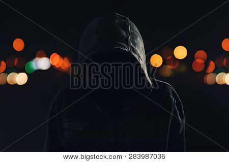 Hooligan With Hoodie And Obscured Face Walking The City Streets At Night, Looking Spooky And Threate