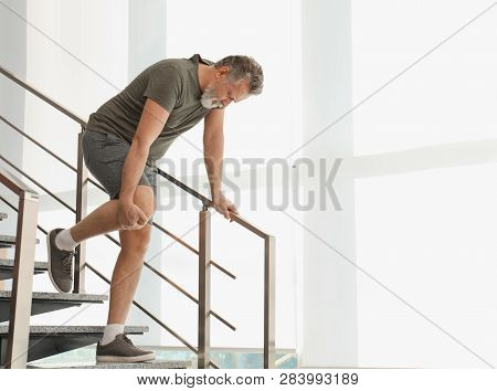 Senior Man Suffering From Knee Pain Indoors. Space For Text