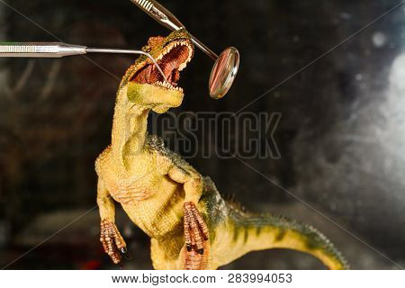 Dinosaur Velociraptor Examine Teeth With Dental Mirror And Probe. The Concept Of Dental Care. Toy Di