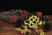 Silk maple leaves, beautiful bouquet of sunflowers, frosted pinecones and orange candle on tabletop with dark background. poster
