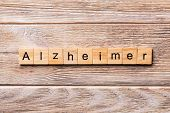Alzheimer word written on wood block. Alzheimer text on wooden table for your desing, concept poster