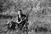 Hunter with rifle looking for animal. Hunter khaki clothes ready to hunt nature background. Hunting shooting trophy. Man charging hunting rifle. Hunting hobby and leisure. Hunting equipment concept poster