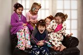 Elementary age girls at slumber party torture brother with hair rollers and makeup. poster