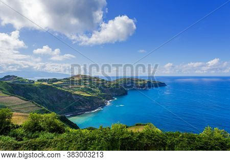View from the Miradouro de Santa Iria on the island of São Miguel in the Azores. The view shows part of the northern coastline with cliffs and green fields on the clifftop.