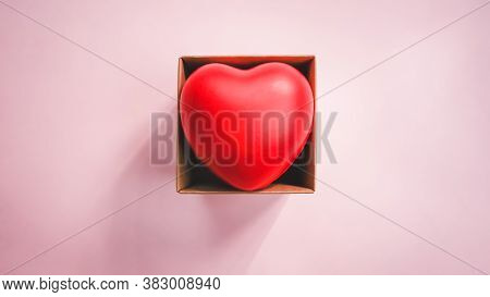 Top View Of Red Heart In The Paper Brown Box With Pink Background. Valentine Day Concept. World Hear
