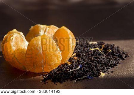 Mandarin Close-up. Next To It Is A Handful Of Medium Leaf Black Tea With Bergamot, Orange Zest And F