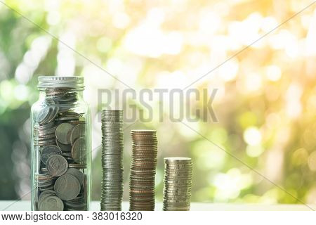 Thai Coin In Glass Bottle With Money Stack Step Up Growing Growth Saving Money. The Concept Of Savin
