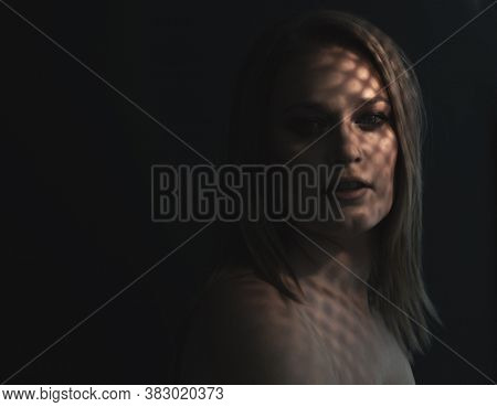 Beautiful mid adult woman with interesting pattern of light and shadow on her face. Beauty female portrait, soft focus