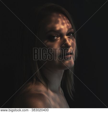 Beautiful mid adult woman with interesting pattern of light and shadow on her face. Beauty female portrait